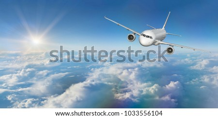 Commercial airplane flying above dramatic clouds. Wide screen format.