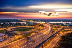 Commercial airplane flying over Beautiful night city, cityscape of Nonthaburi bridge in Bangkok Thailand road for transportation at twilight