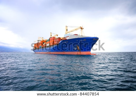 commercial container ship with dramatic sky