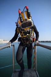 Commercial Diver entering the water fully equipped