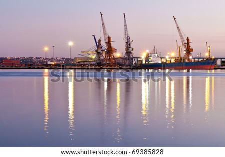 Commercial docks at sunset with a ship and cranes