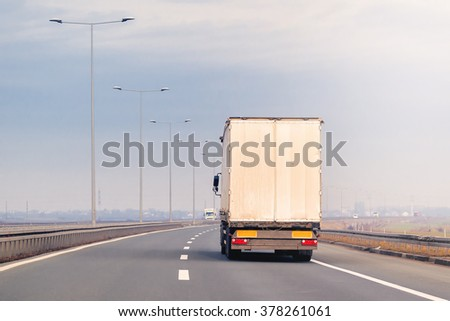 Commercial industrial trailer truck in motion on Eastern Europe freeway on cloudy autumn afternoon, cargo transportation. #378261061