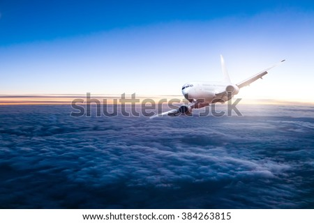 Commercial jet aeroplane flying above clouds