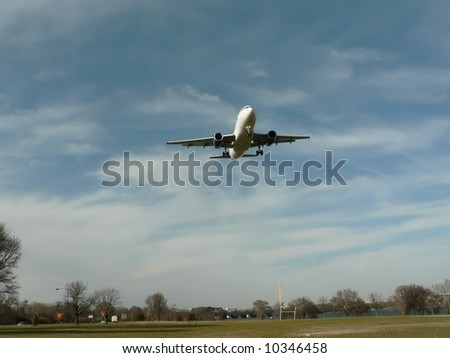 commercial jet in flight in a landing pattern over a park in Washington,D.C. with the Monument in the distance.