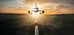 Commercial jetliner landing on runway. Modern and fastest mode of transportation. Dramatic sunset sky on background