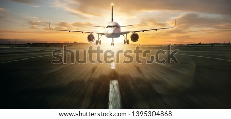 Commercial jetliner landing on runway. Modern and fastest mode of transportation. Dramatic sunset sky on background