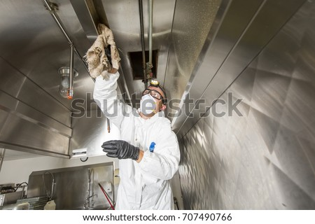 Commercial kitchen worker washing up at sink in professional kitchen