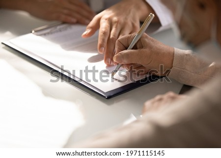 Commercial medicine. Close up of aged woman patient hand signing medical insurance contract at doctor office. Female medic show retired lady client place to put signature on healthcare coverage policy