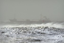 Commercial merchant ship sailing in a stormy weather in the ocean. No people. Copy space
