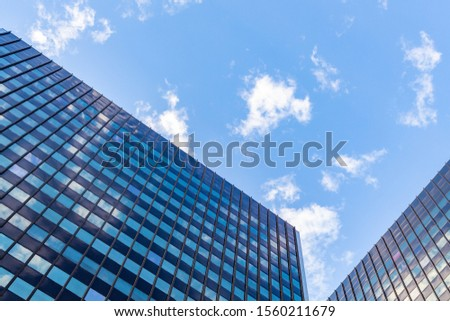 Commercial office buildings are viewed from the ground, looking up. A blue sky with a scattering of white clouds can be seen above, and in the reflecting windows. Their roofs of angle in and down.