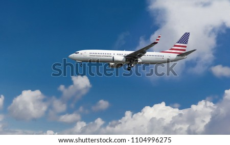 Commercial passenger aircraft with American flag on the tail. Blue cloudy sky in the background