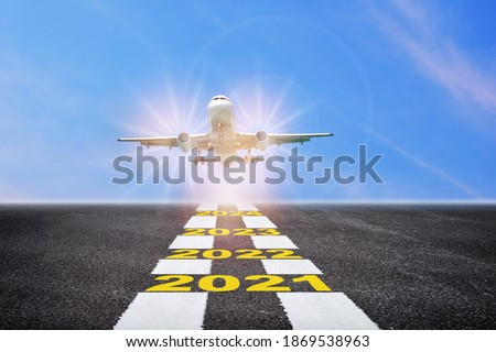 Commercial plane ready for landing or taking off with year 2021 to 2024 written on runway background. Airplane business recovery after covid-19 impact to airplane transport industry crisis concept Foto stock ©
