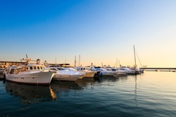 Commercial port of yachts and motor boats in Black sea at sunset.