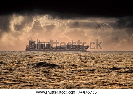 Commercial Ship crossing ocean in a stormy sunset
