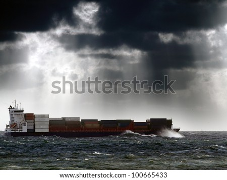 Commercial Ship crossing ocean in a stormy sunset with sun beams; enhanced sky