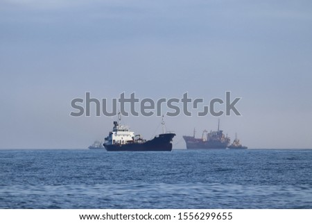Commercial ships moving on the route. Tugboats towing the old rusty wreck ship for ship breaking and tankermoving in oppodite direction. Calm blue sea, sunny day.