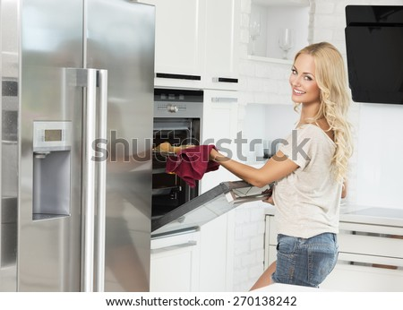 commercial shot of young girl , smiling and cooking with oven , in her luxury kitchen