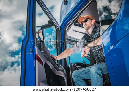 Commercial Truck Driver on Duty. Caucasian Semi Truck Driver Awaiting New Cargo in the Parking Area.