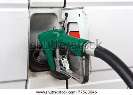Commercial vehicle is being filled up with fuel.