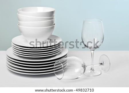 Commercial white plates and bowls stacked with crystal wine glasses