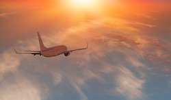 Commerical passenger airplane over the clouds with amazing sunset - Travel by air transport