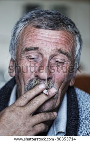 Common elderly man with mustache smoking cigarette