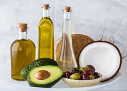 Common healthy cooking oils including avocado oil, olive oil and coconut oil. Healthy fat concept.