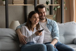 Common interests. Bonding millennial family couple hugging on sofa at living room having pleasure watching movie on tv. Friendly loving young spouses enjoy video film soccer match on weekend evening
