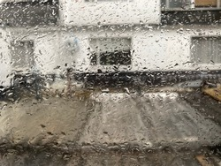 Common Old House through a looking glass with rainy drops during daylight.