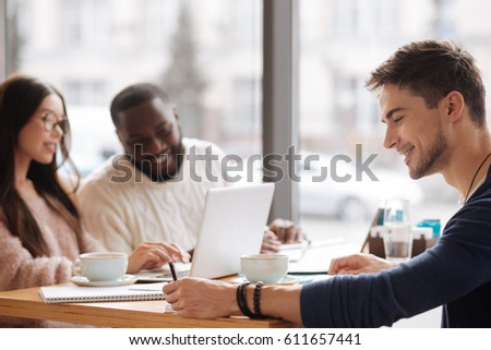Common project. Side view of young smiling man taking notes while studying together with his fellow students at cafeteria.
