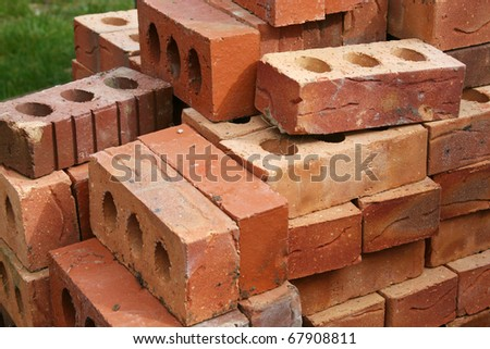 Common quality building bricks stacked ready for use.