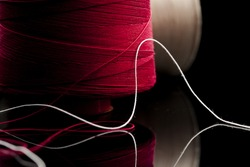 common thread, cotton yarn red and white leaning on black table mirror. reel of cotton spool of red and white cotton blurred in the background