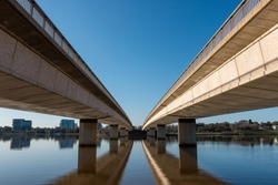 Commonwealth Avenue Bridge, Canberra, across Lake Burley Griffin, with symmetrical reflections in water. Blue sky and warm afternoon, pre-sunset light hitting concrete bridge. View from south side.