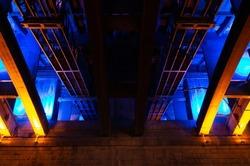 Communal bridge under blue and golden lights. Illumination underbridge space at night. Abstract industrial background