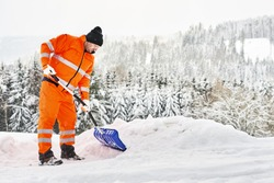 Communal service worker in uniform with a shovel clears snow in winter
