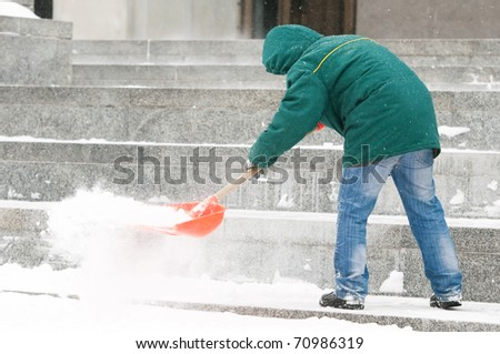 communal services worker in uniform shoveling snow in winter snowstorm