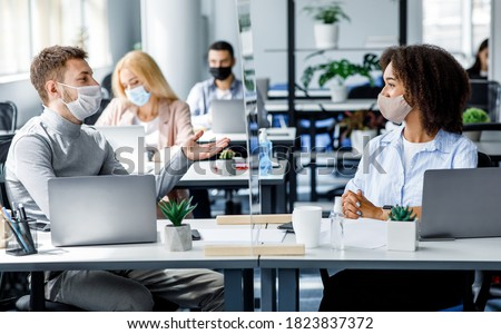 Communication and meeting in office after returning from covid-19 quarantine. Young guy and african american woman in protective mask talking through glass board at workplace with laptops in office
