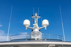 Communication antennas with navigation equipment, radar on the upper deck of the luxury white cruise ship.  There is a Thai flag with clear blue sky in the sunny day.