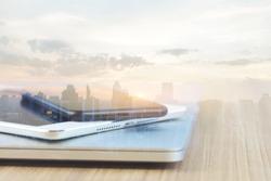 communication device stack on desk and city background reflect modern technology concept