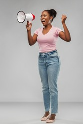 communication, feminism and human rights concept - african american young woman speaking to megaphone over grey background