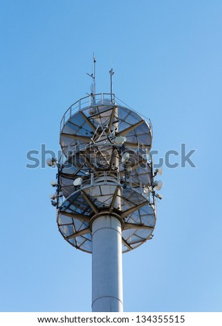 Communication mast for various antennae and dishes against blue sky