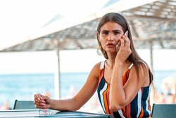 Communication. Portarit of a stylish woman with a scared look is sitting in a summer cafe on the beach and talking on the phone. Concept of fraudulent calls