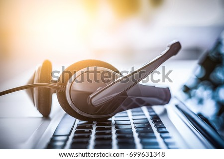 Communication support, call center and customer service help desk. VOIP headset on laptop computer keyboard. #699631348