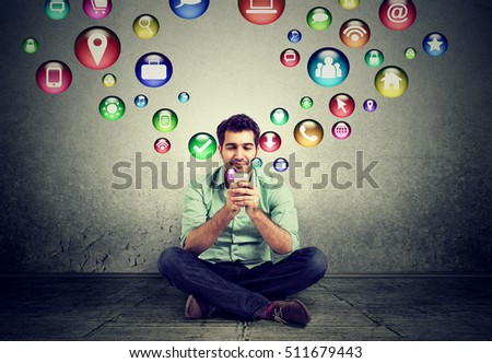 communication technology high tech concept. Happy man sitting on a floor using texting on smartphone social media application icons flying out of cellphone isolated grey wall background. 4g data plan