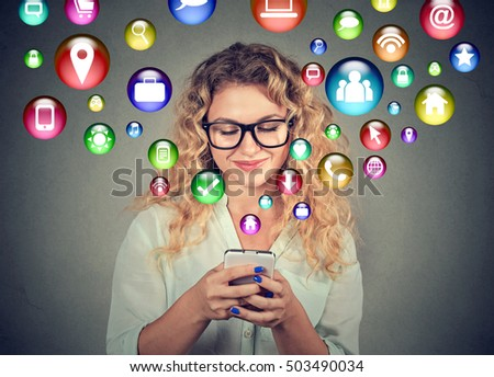 communication technology mobile high tech concept. Happy young woman using texting on smartphone with social media application symbols icons flying out of screen isolated on grey background