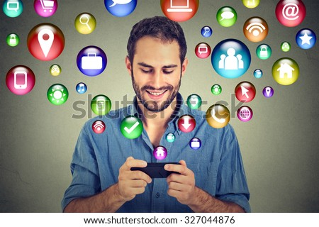 communication technology mobile phone high tech concept. Happy man using texting on smartphone social media application icons flying out of cellphone isolated grey wall background. 4g data plan