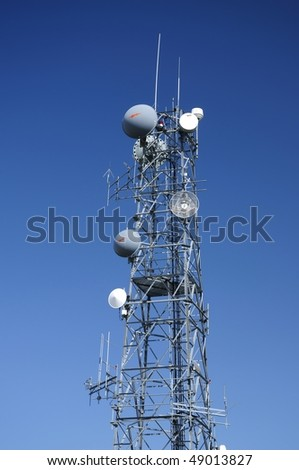 Communication tower over a deep blue sky.