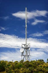 Communication tower radio mast with antenna aerial  against a background of the blue sky.
