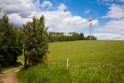 Communication tower - transmitter and lookout tower in meadows. Beautiful spring day.