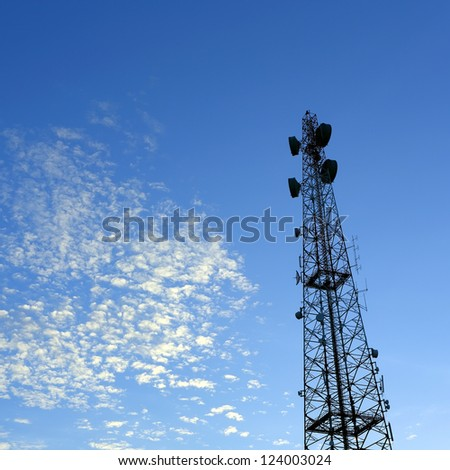 Communication tower under blue sky with clouds